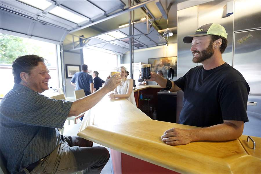 Brewmaster & Owner Justin Marx sharing a glass with a patron. Photo c/o Toledo Blade